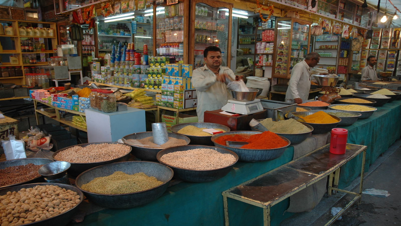 Man selling spices in front of a store in India