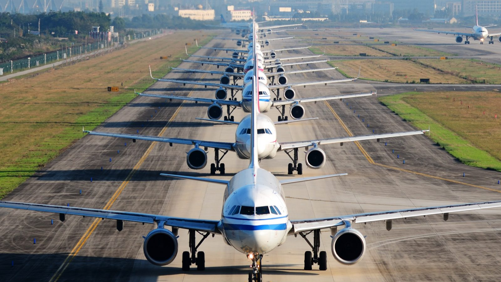 The image depicts several planes lined up on a runway.
