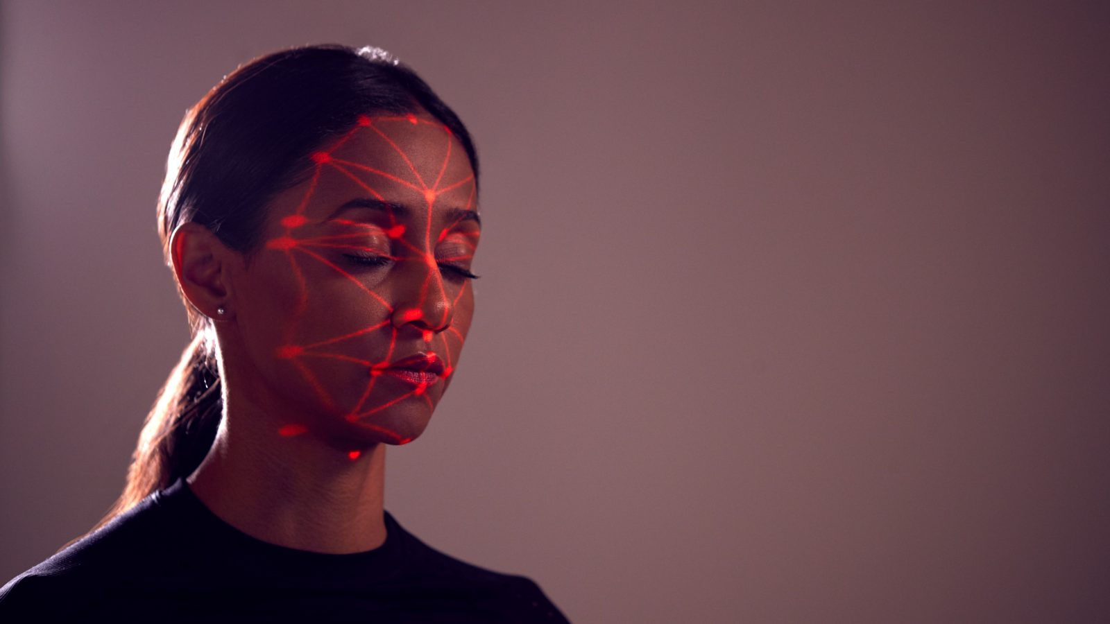 Image shows a woman's face with her face being scanned by red laser lights.