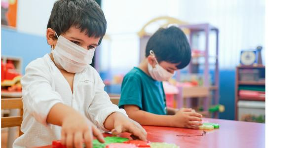 Two young children studying in masks