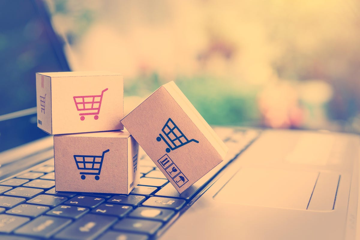 Image depicts shopping carts on cardboard boxes, with a laptop in the background. Representes e-commerce,
